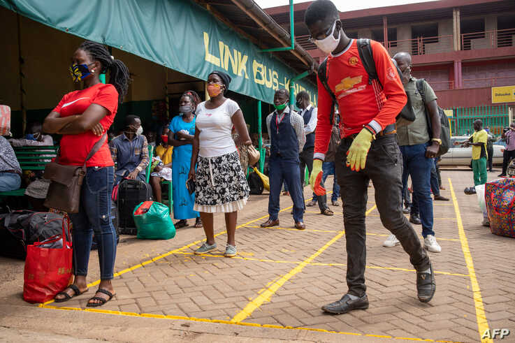 Travellers queue to buy bus tickets while adhering to social distancing measures to curb the spread of the COVID-19 coronavirus…