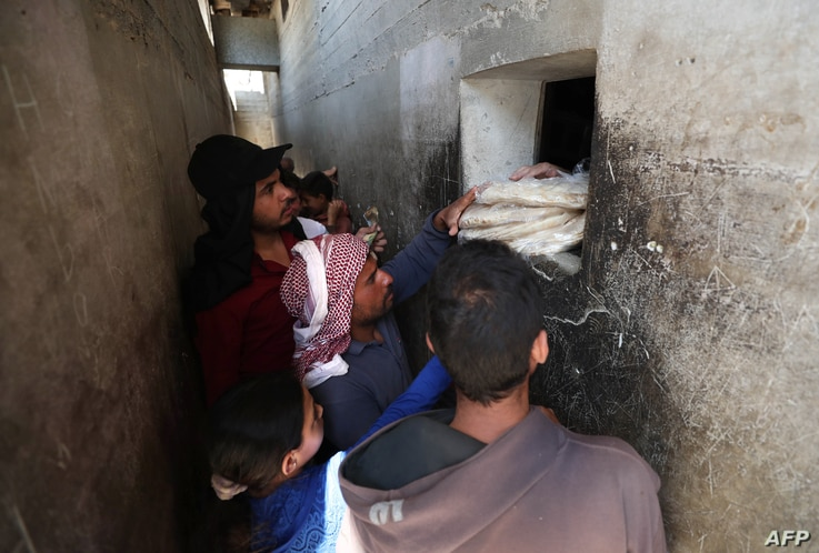 Syrians buy bread at a shop in the town of Binnish in the country's northwestern Idlib province on June 9, 2020. - Syrians held…