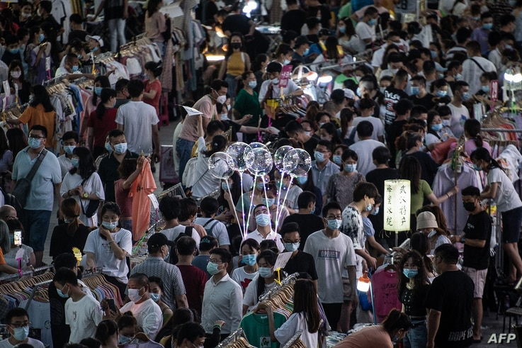 This photo taken on June 10, 2020 shows people visiting an outdoor market in Wuhan in China's central Hubei province. - Snacks,…