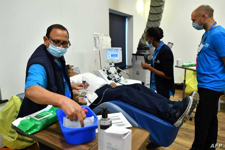 Aubrey Dhanraj, a plasma donor lies on reclining seat to give convalescent plasma for coronavirus treatment at a newly opened…
