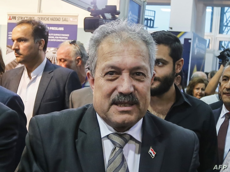 (FILES) In this file photo taken on October 2, 2018, Syria's then-Water Resources Minister Hussein Arnous attends the Trade…