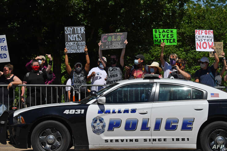 Protesters hold placards near Gateway Church Dallas Campus as US President Donald Trump arrives for a roundtable with faith…