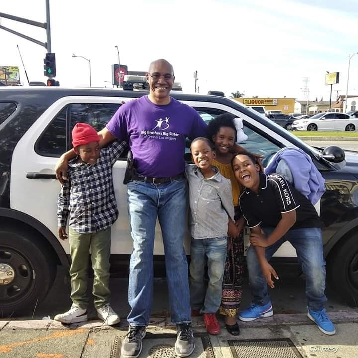 Sergeant Keith Mott poses for a photo with a mentee and the child's siblings during a Big Brother Big Sisters of America activity.
