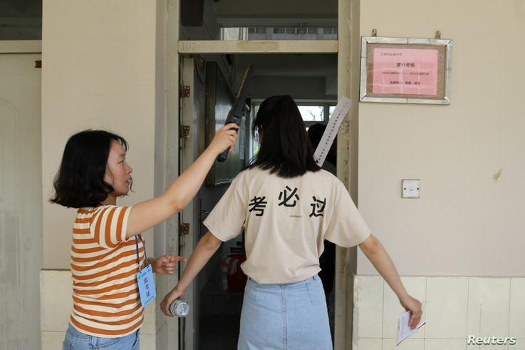 A student is checked with a metal detector before she enters a classroom for the annual national college entrance examination,…