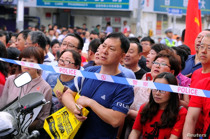 "Parents wait behind police cordon outside the venue for the annual national college entrance examination, or ""gaokao"", in…"