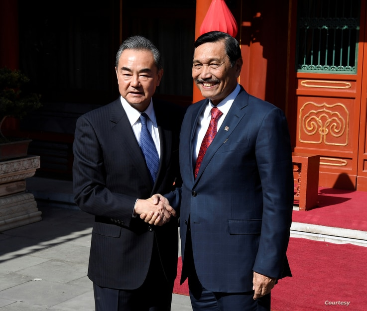 FILE - China's Foreign Minister Wang Yi shakes hands with Indonesia's Coordinating Minister for Maritime Affairs Luhut Pandjaitan before a meeting at the Diaoyutai State Guesthouse in Beijing, China, Oct. 24, 2018.