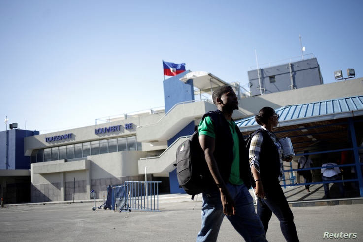 Workers with the Haiti's Ministry of Public Health and Population walk outside of International Airport Toussaint Louverture
