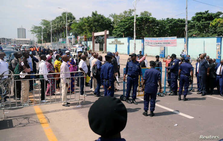 Congolese police officers control civilians during a total lockdown amid concerns about the spread of the coronavirus disease …
