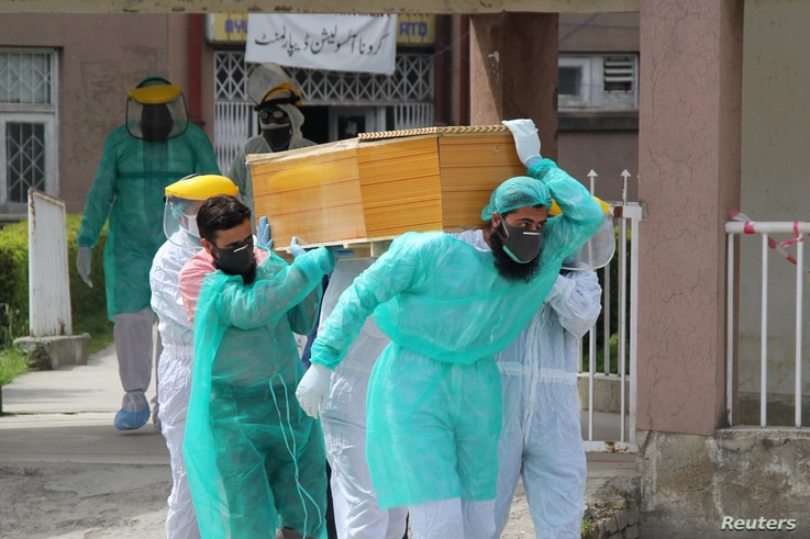 Health workers wearing protective gear move a body of a man who died from the coronavirus disease (COVID-19), outside an…