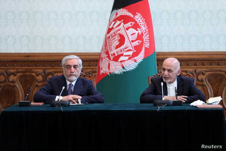Afghanistan's President Ashraf Ghani and his rival Abdullah Abdullah attend a ceremony to sign a political agreement in Kabul,…