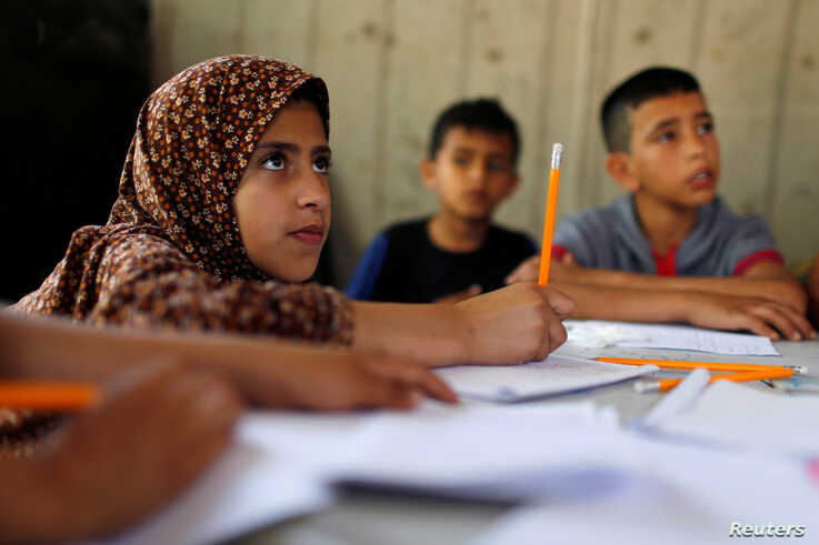 Children attend an Arabic language lesson given by a Palestinian school girl Fajr Hmaid, 13, as schools are shut due to the…