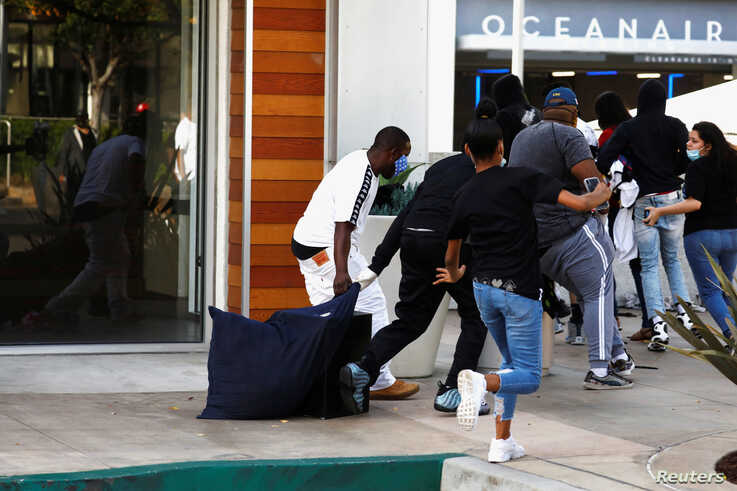 People run with a bag of items during nationwide unrest following the death in Minneapolis police custody of George Floyd, in…