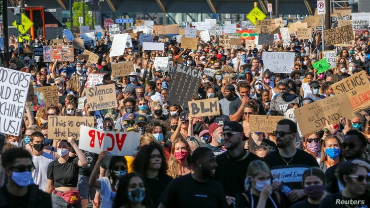 Thousands of protesters march from downtown to the site of the arrest of George Floyd, who died while in police custody in…