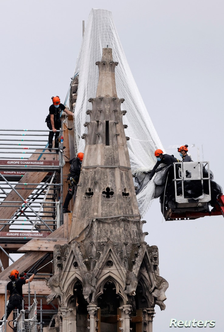 Workers prepare to remove damaged scaffolding elements from the remains of the burnt roof of Notre Dame Cathedral in Paris,…