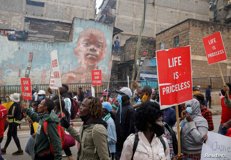 Protesters hold placards during a demonstration against police killings and brutality, in the Mathare slum in Nairobi, Kenya,…