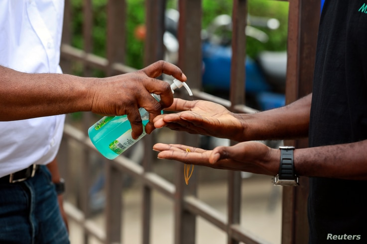 A security guard pours hand sanitising gel into a shopper's hands as he enters the Tejuoso shopping complex at the Yaba market,…
