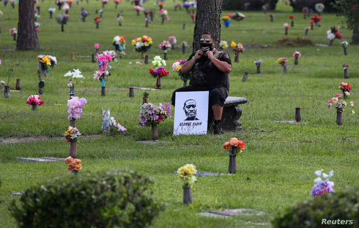 A mourner adjusts his protective face mask as he waits for the funeral for George Floyd at the Houston Memorial Gardens…