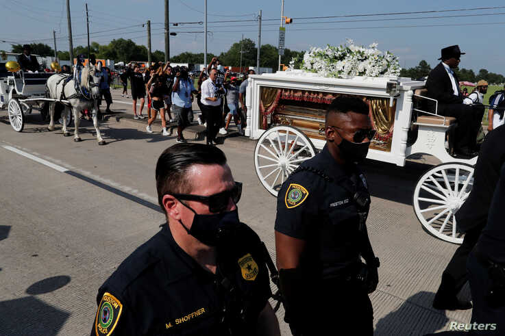 Police officers walk next to the horse-drawn carriage carrying the casket containing the body of George Floyd, whose death in…