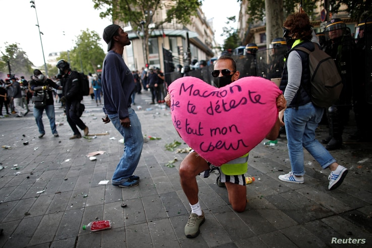 "A demonstrator holds a heart reading ""Macron, I hate you with all my heart"" during a protest against police brutality and the…"