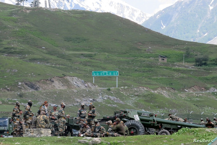 Indian army soldiers rest next to artillery guns at a makeshift transit camp before heading to Ladakh, near Baltal, southeast…