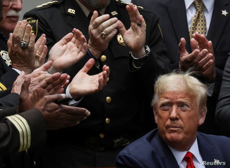U.S. President Donald Trump listens to applause after signing an executive order on police reform during a ceremony in the Rose…