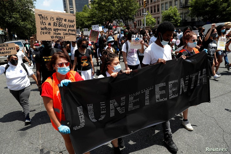 People carry a banner as they take part in events to mark Juneteenth, which commemorates the end of slavery in Texas