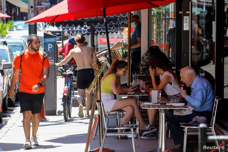 Diners eat lunch in outdoor seating at a restaurant in the Little Italy section of Manhattan on the first day of the phase two…