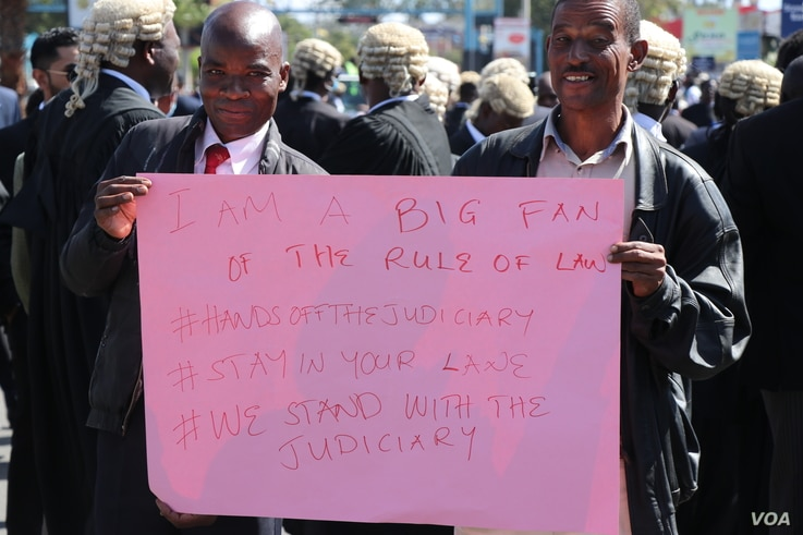 Protesters carry a sign during a demonstration against what they call government interference in the judiciary, in Blantyre, Malawi, June 17, 2020. (Lameck Masina/VOA)