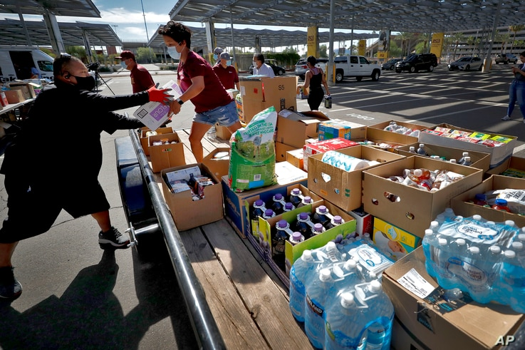Volunteers prepare donations for delivery to those affected by COVID-19 on tribal lands Thursday, June 25, 2020, in Tempe, Ariz…