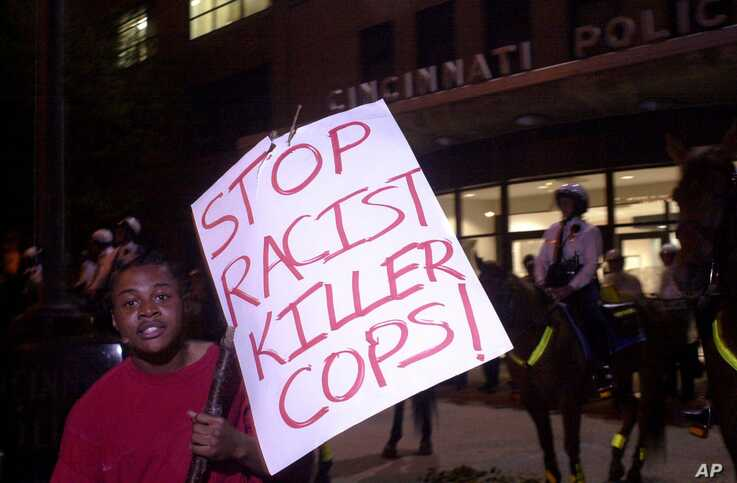 An anti-police protester stands in front of mounted Cincinnati Police, dressed in riot gear, outside police headquarters during…