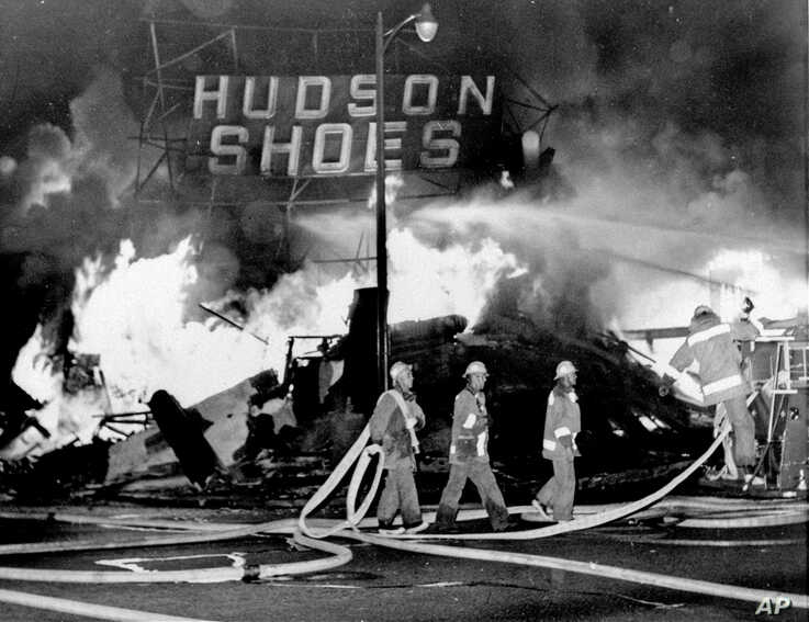 FILE - In this Aug. 14, 1965 file photo, firefighters battle a blaze set in a shoe store that collapses in flames during rioting