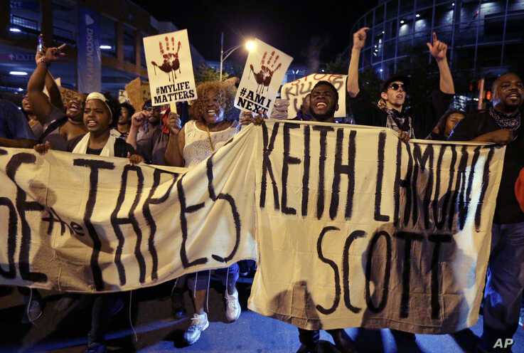 FILE - In this Friday, Sept. 23, 2016 file photo, protesters shout as they march in the streets of Charlotte, N.C., to protest…