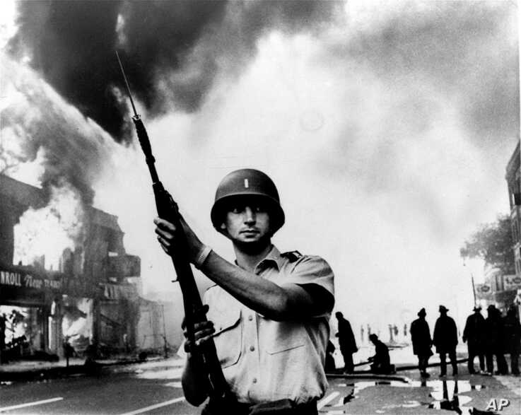 FILE - In this July 1967 photo, a National Guardsman stands at a Detroit intersection during riots in the city. Detroit…