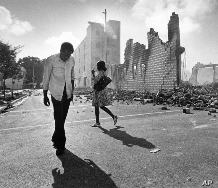 FILE - In this May 19, 1980, photo, people walk past ruins in the Culmer section of Miami after rioting over the acquittal of…