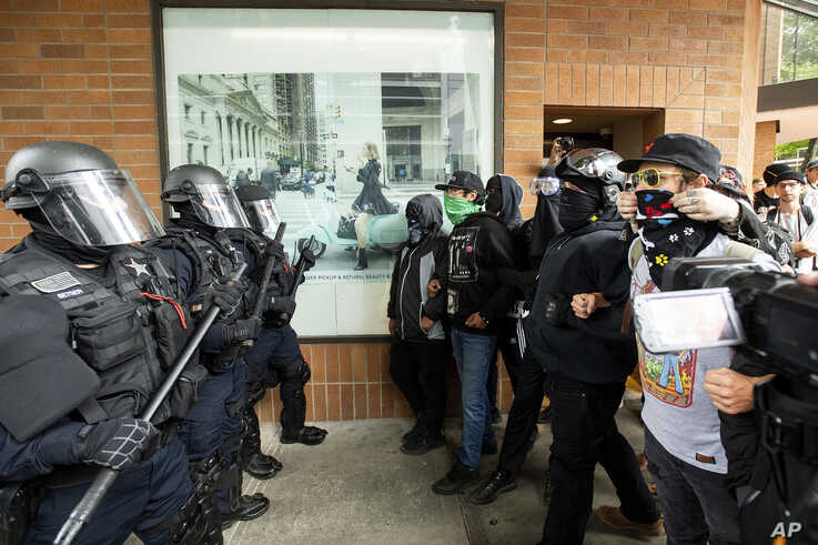 """Police officers face off against protesters opposed to right-wing demonstrators following an """"End Domestic Terrorism"""" rally in…"""
