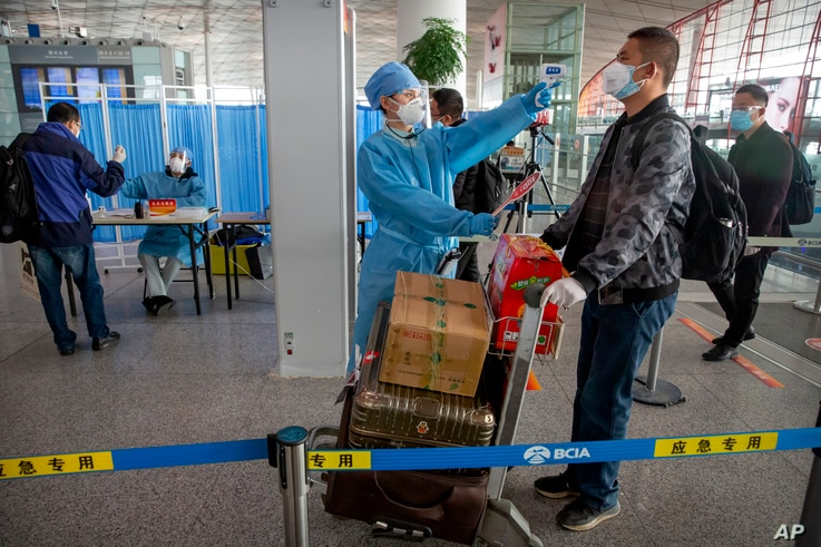 A worker in a protective suit takes the temperature of a traveler at Beijing Capital International Airport in Beijing, Friday,…