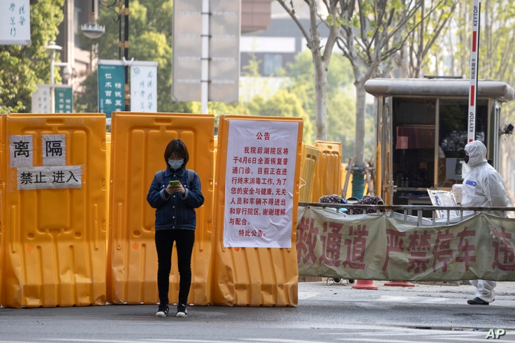 A woman wearing a mask stands near an entrance to the Wuhan Central Hospital in Wuhan in central China's Hubei province…
