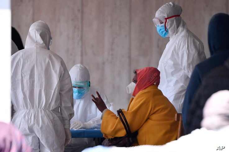 A woman with a face mask speaks with medical staff in protective clothing at a refugee camp after two suspect cases of coronavirus were allegedly confirmed and the area cordoned off as a red zone, on the outskirts of Rome, April 8, 2020.