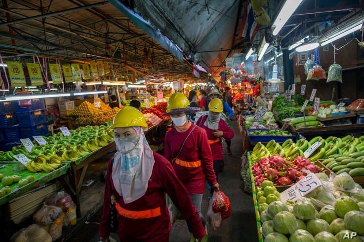 Migrant construction workers, wearing face masks to protect against coronavirus, walk through a market
