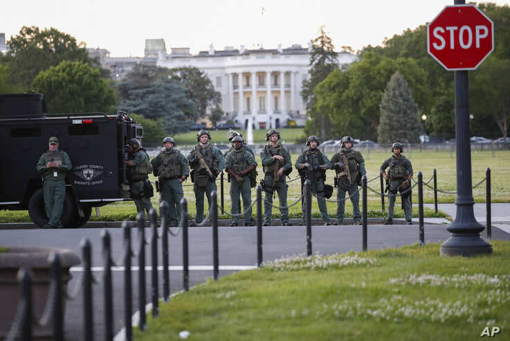 Law enforcement officers from Calvert County Maryland Sheriff's Office standing on the Ellipse are of the White House