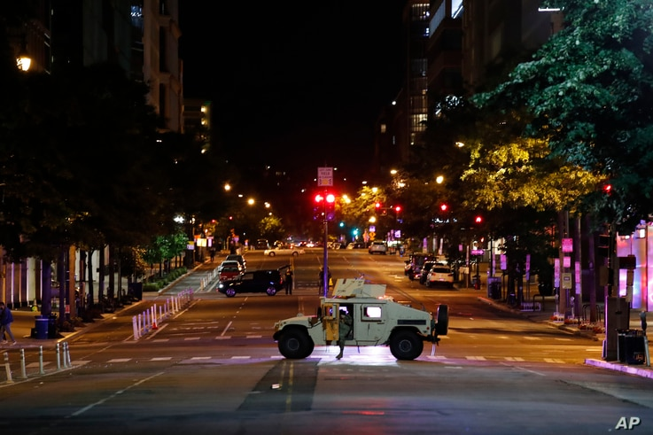 A Humvee blocks an intersection along K Street in downtown Washington as demonstrators protest the death of George Floyd, June 1, 2020, in Washington.