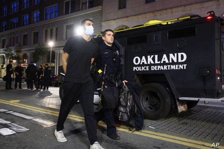 A police officer detains a demonstrator in Oakland, Calif., on June 1, 2020, during a rally for George Floyd.