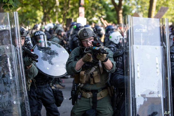 An Arlington County Police officer aims as demonstrators are moved back after gathering to protest the death of George Floyd, June 1, 2020, near the White House in Washington.