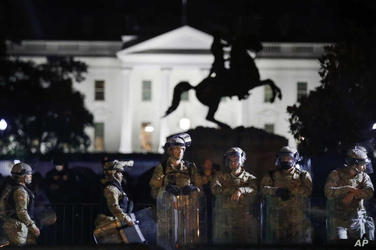 A line of DC National Guard members stand in Lafayette Park as demonstrators gather to protest the death of George Floyd.
