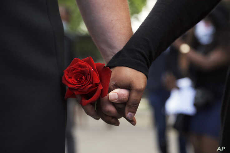 The fiancé of George Floyd, left, holds hands with a supporter at North Central University after a memorial…