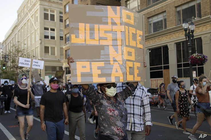 A woman holds up a sign in Oakland, Calif., June 4, 2020, during a protest over the death of George Floyd.