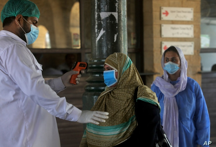 A railway worker checks the body temperature of a woman wearing a protective mask to help curb the spread of the coronavirus,…