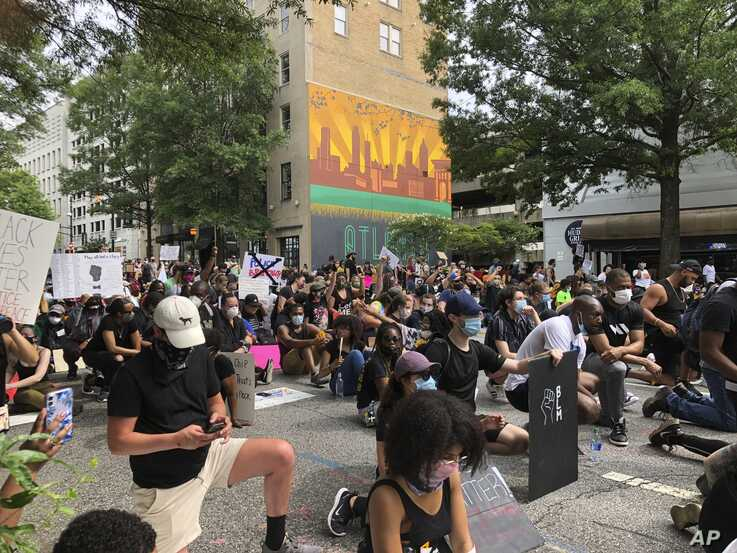 Protesters pause in a moment of silence during a march Saturday, June 6, 2020, in downtown Atlanta. Demonstrations continue across the United States in protest of racism and police brutality, sparked by the May 25 death of George Floyd in police custody in Minneapolis.