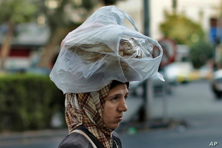 FILE - A woman carries bread on her head while she crosses a street in the Syrian capital,…