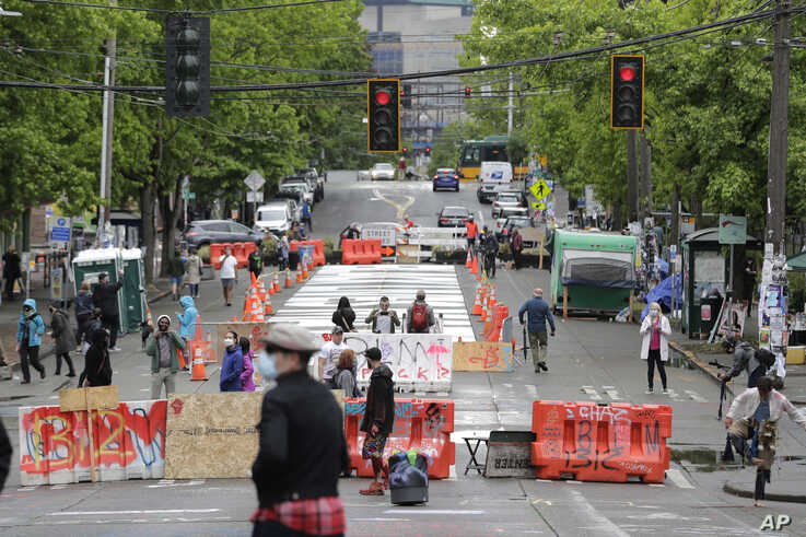 People walk past barricades on a street near Cal Anderson Park, Thursday, June 11, 2020, inside what is being called the …